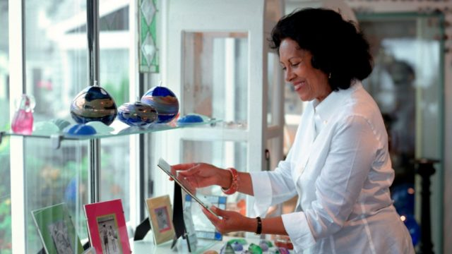 Smiling lady looking at pictures in a gift shop